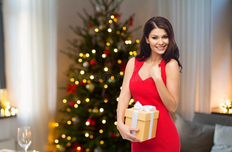 Härlig kvinna med julgåvan hemma fotografering för bildbyråer