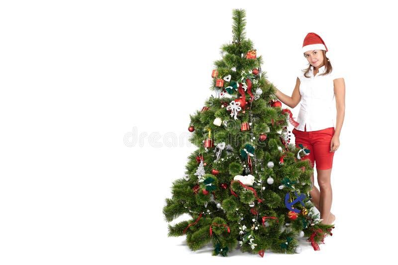 Härlig kvinna med jultomtenhatten som dekorerar julgranen som isoleras på vit bakgrund royaltyfri fotografi