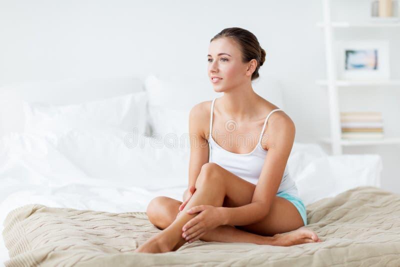 Härlig kvinna med kala ben på säng hemma fotografering för bildbyråer