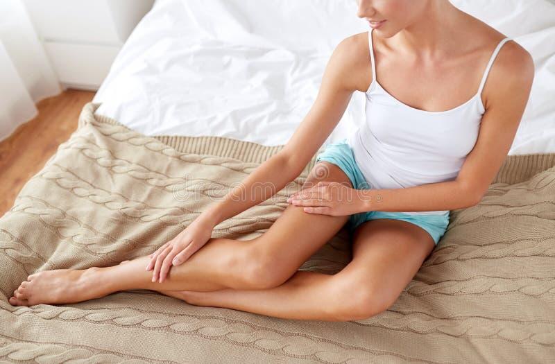 Härlig kvinna med kala ben på säng hemma arkivbild