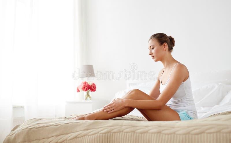 Härlig kvinna med kala ben på säng hemma arkivfoto
