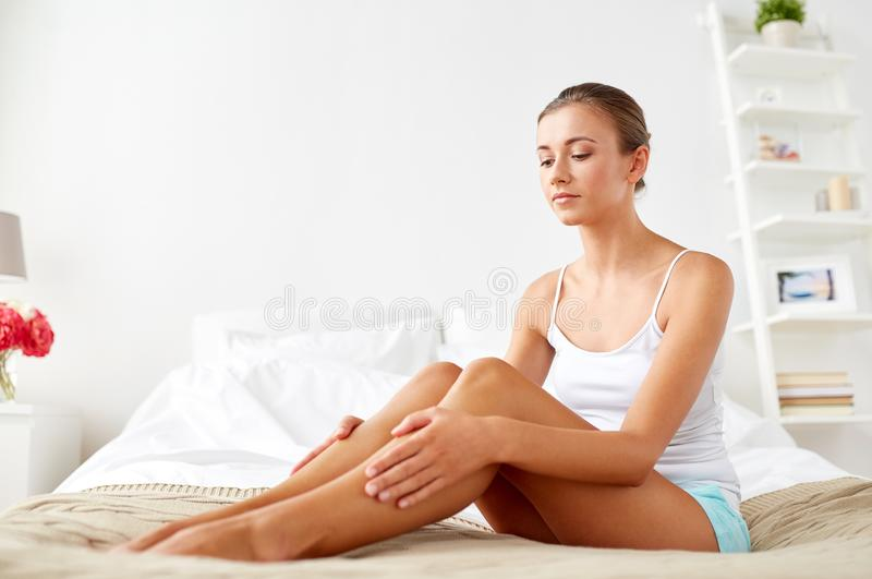 Härlig kvinna med kala ben på säng hemma royaltyfria bilder