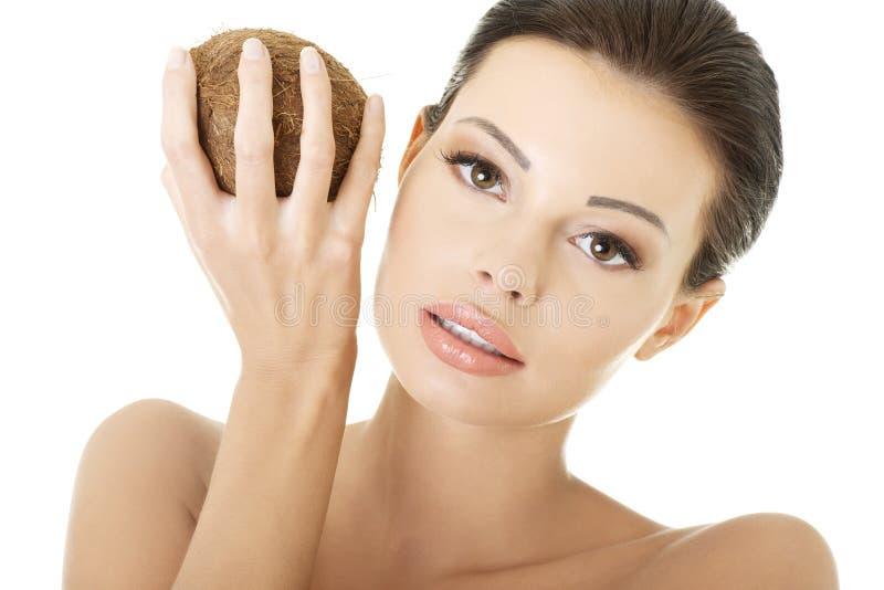 Härlig kvinna med kokosnöten i händer royaltyfri foto