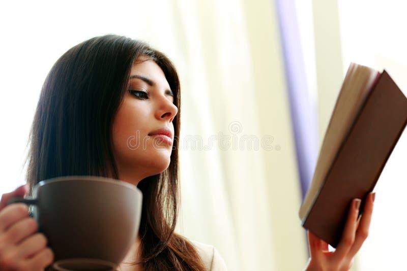 Härlig kvinna med kopp kaffeläseboken royaltyfria bilder