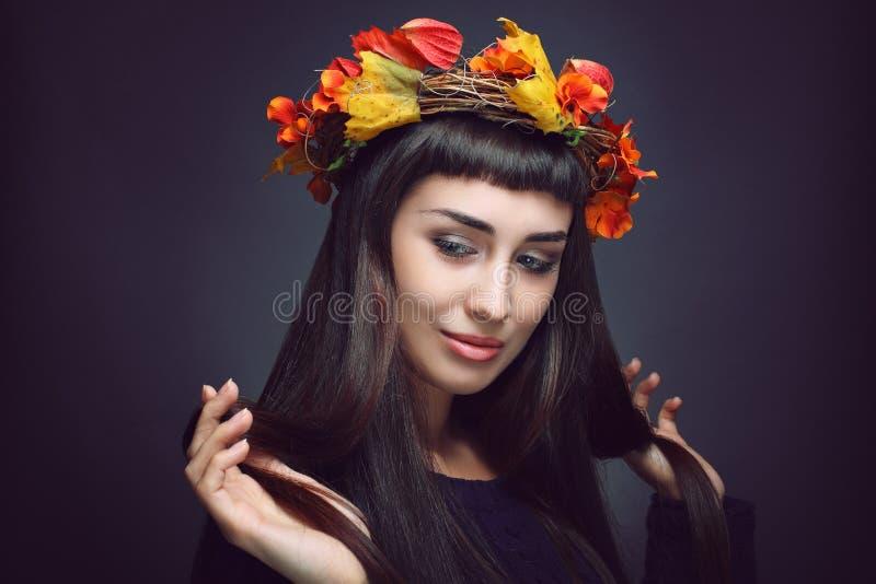 Härlig kvinna med kronan för höstsidor arkivfoto