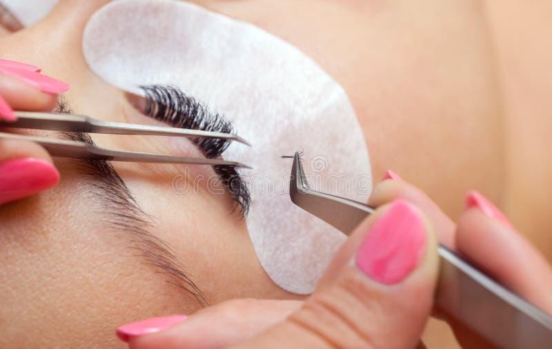 Härlig kvinna med långa ögonfrans i en skönhetsalong Ögonfransförlängningstillvägagångssätt fotografering för bildbyråer
