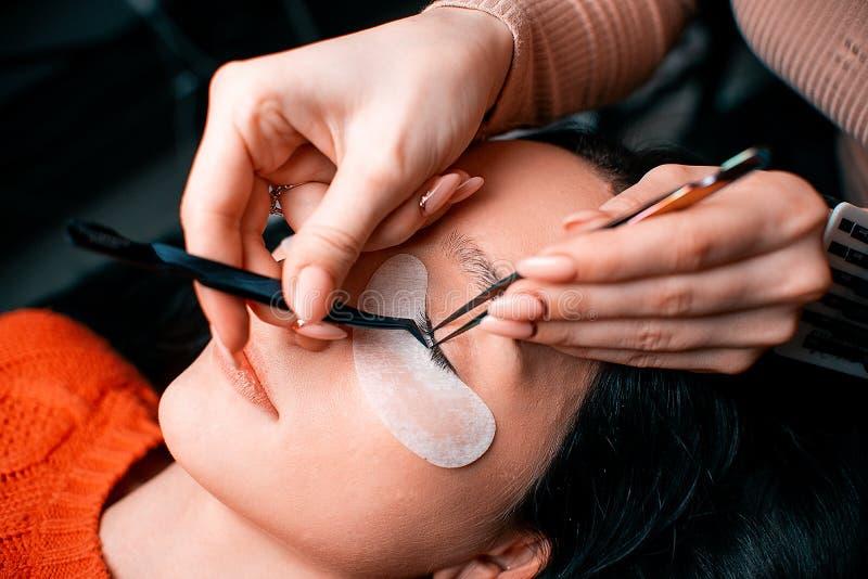 Härlig kvinna med långa ögonfrans i en skönhetsalong Ögonfransförlängningstillvägagångssätt Snärtar stänger sig upp royaltyfri foto
