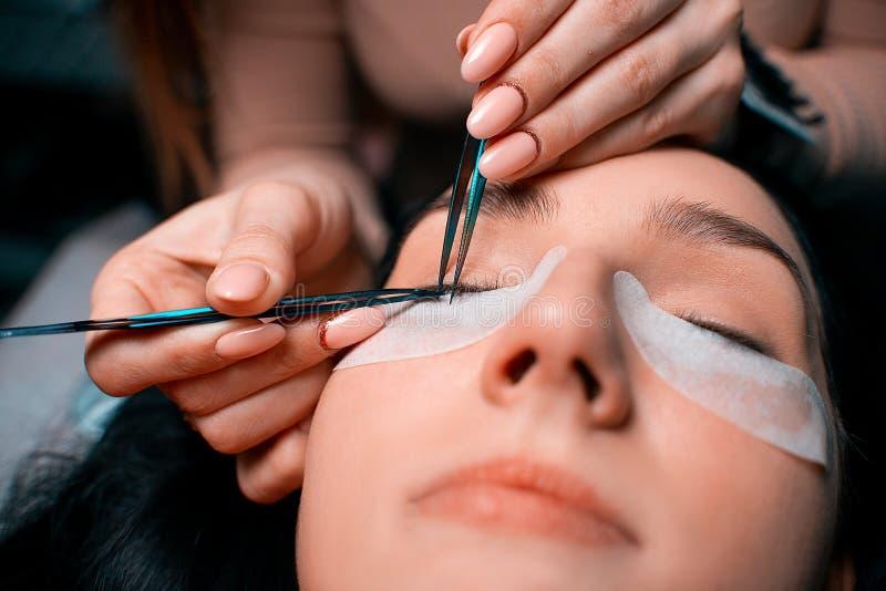 Härlig kvinna med långa ögonfrans i en skönhetsalong Ögonfransförlängningstillvägagångssätt Snärtar stänger sig upp arkivbilder