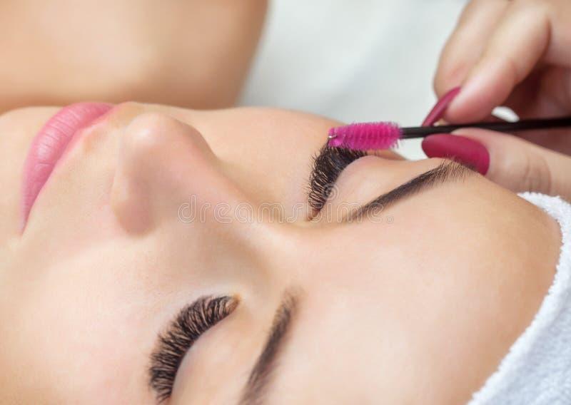 Härlig kvinna med långa ögonfrans i en skönhetsalong Ögonfransförlängningstillvägagångssätt royaltyfria foton
