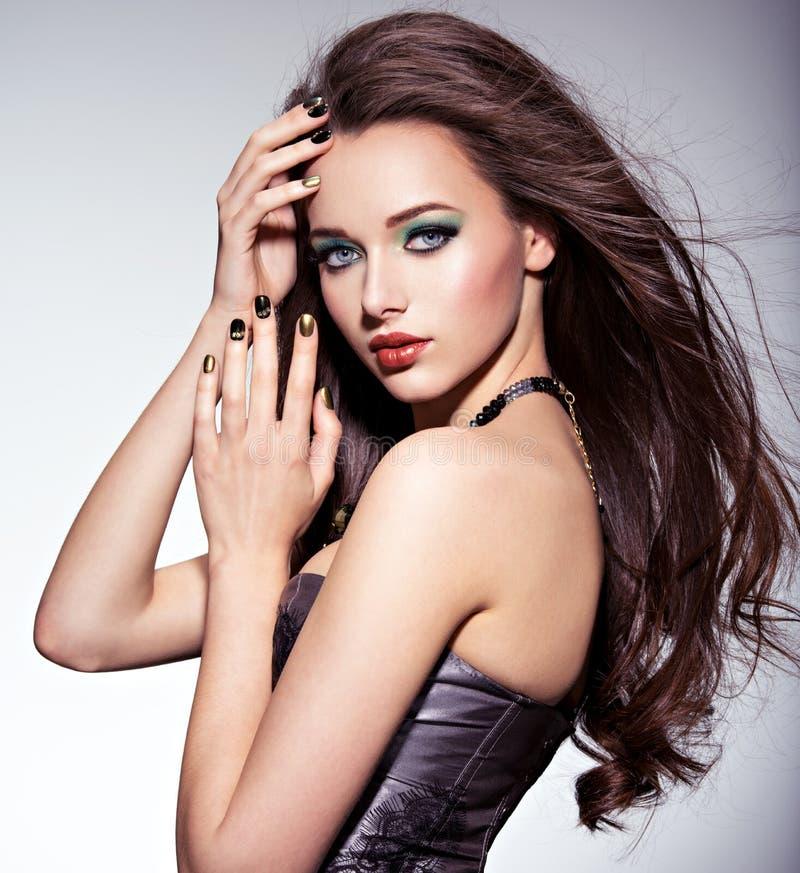 Härlig kvinna med långa bruna hår och grönt smink arkivbild