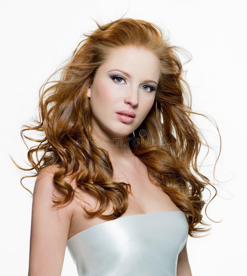 Härlig kvinna med långa lockig-hövdade hår royaltyfria bilder
