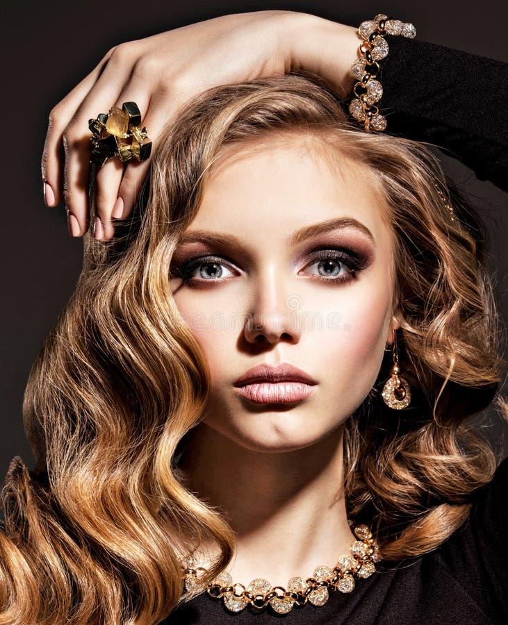 Härlig kvinna med långa lockigt hår- och guldsmycken royaltyfri foto