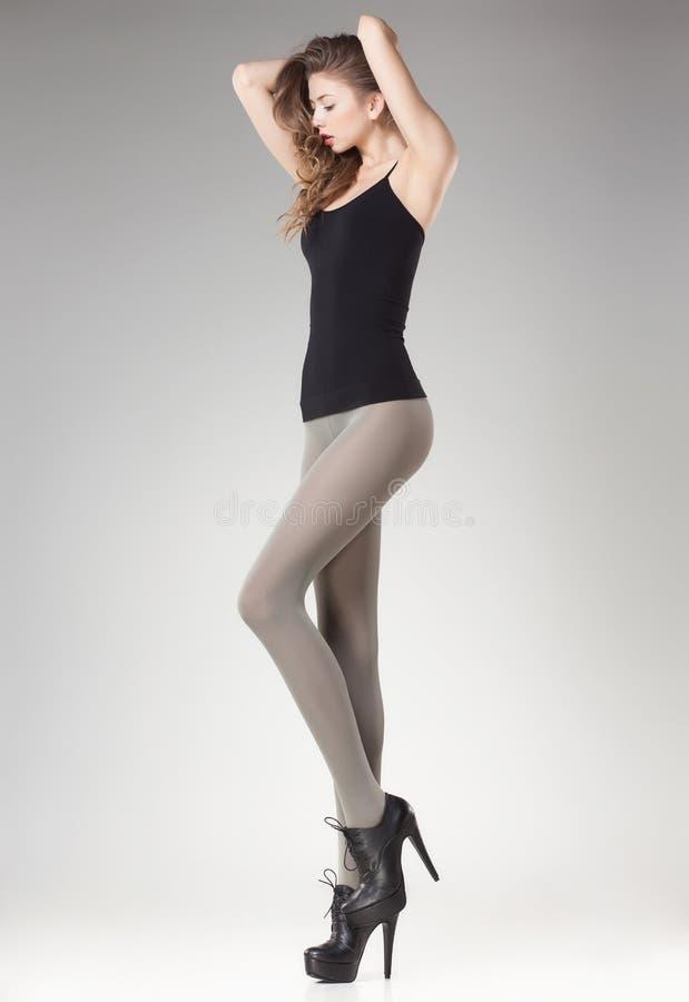Härlig kvinna med långa sexiga ben i strumpor och höga häl arkivfoton