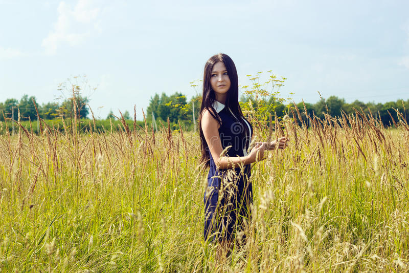 Härlig kvinna med långt anseende för mörkt hår i solig cornfield royaltyfri bild