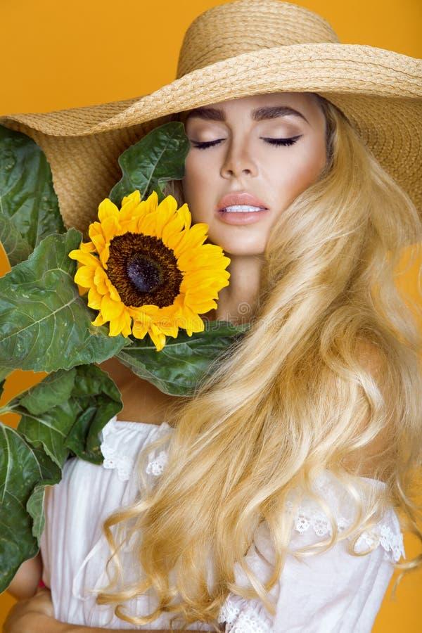 Härlig kvinna med långt blont hår och att bära en vit klänning och hatt, hållande solrosor royaltyfri fotografi