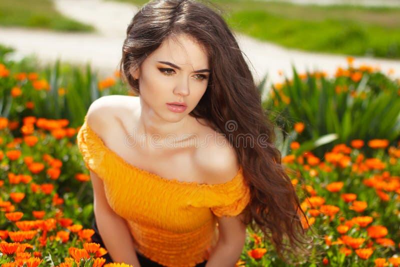 Härlig kvinna med långt brunt hår över blommafält. Closeup arkivbilder