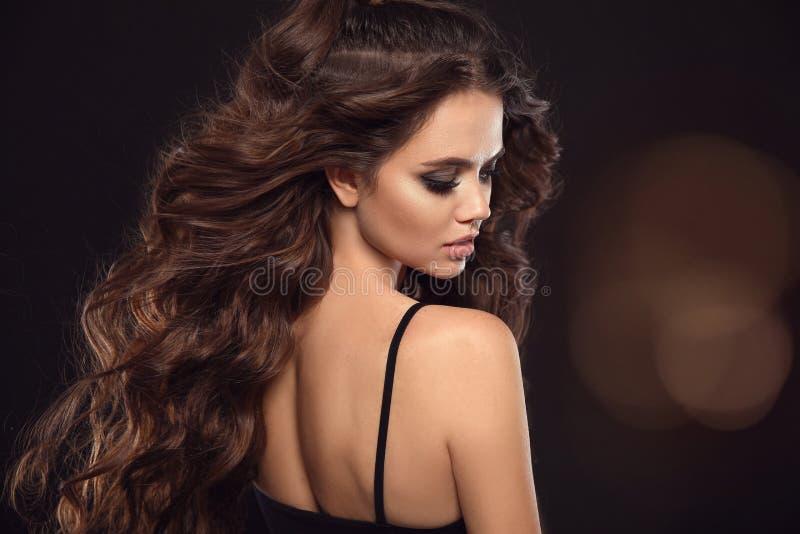 Härlig kvinna med långt brunt lockigt hår Closeupstående med en nätt framsida av unga flickan Modemodell med manikyr arkivbilder