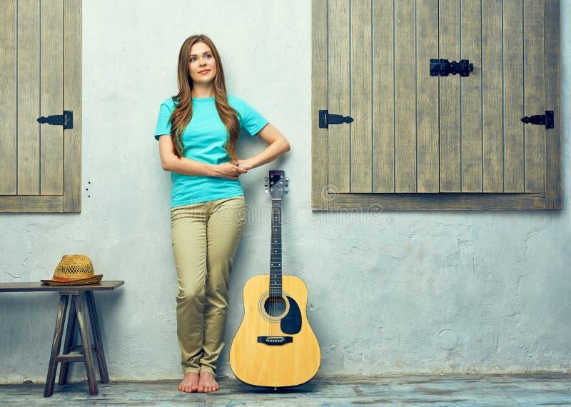 Härlig kvinna med långt hår som poserar mot väggen fotografering för bildbyråer