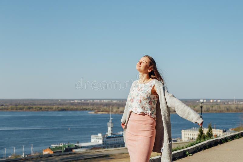 Härlig kvinna med långt hår som tycker om stadssikten från bron på en solig dag arkivfoton