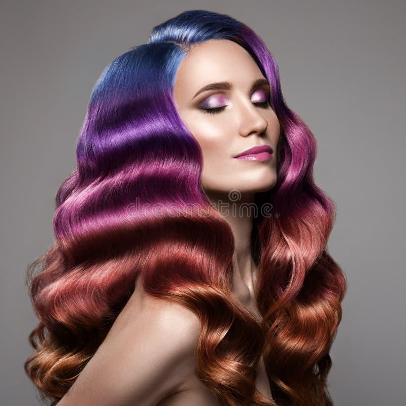 Härlig kvinna med långt lockigt färgrikt hår royaltyfri bild