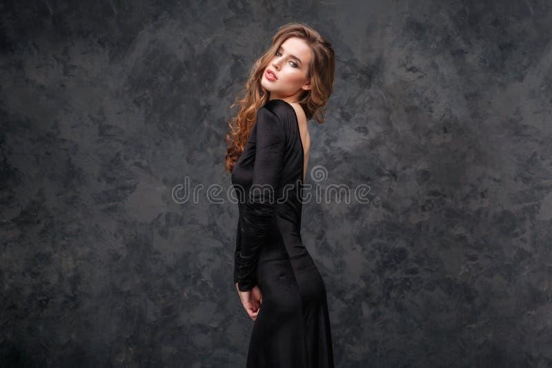 Härlig kvinna med långt lockigt hår i aftonsvartklänning arkivfoton