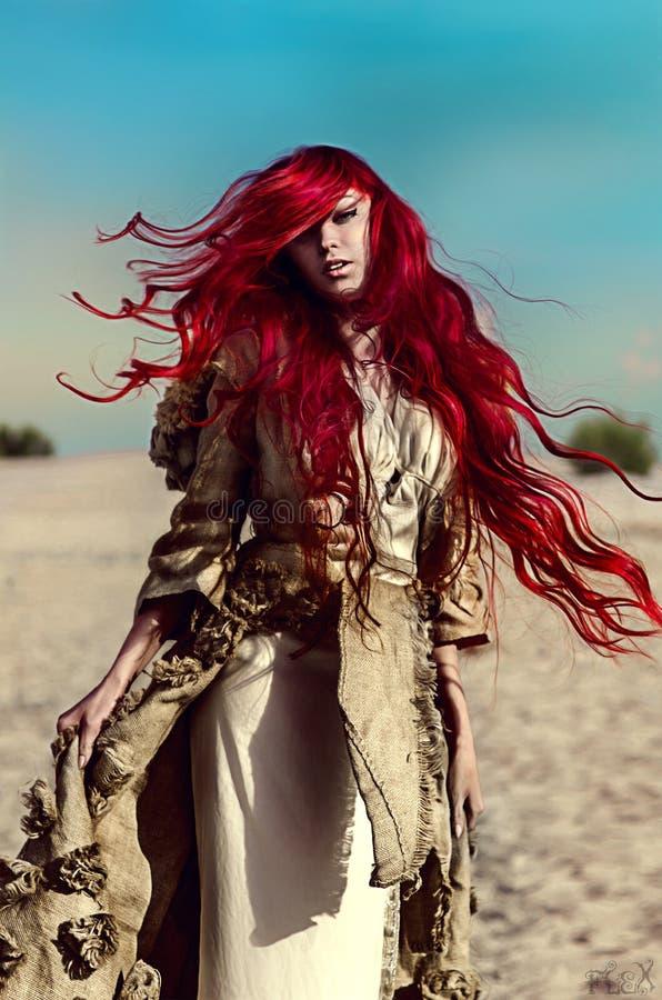 Härlig kvinna med långt rött hår royaltyfri foto