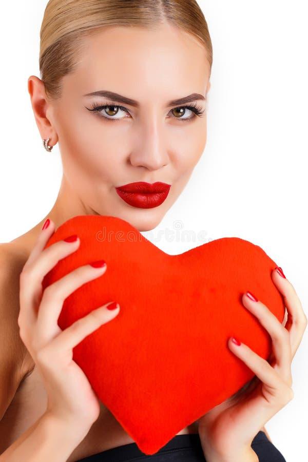 Härlig kvinna med ljus makeup och röd hjärta arkivbild