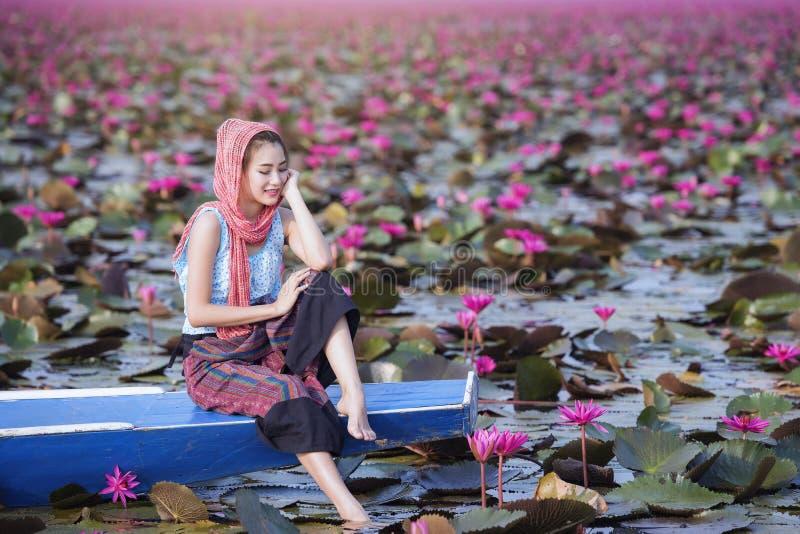 Härlig kvinna med lotusblommablomman på det röda lotusblommahavet arkivbild