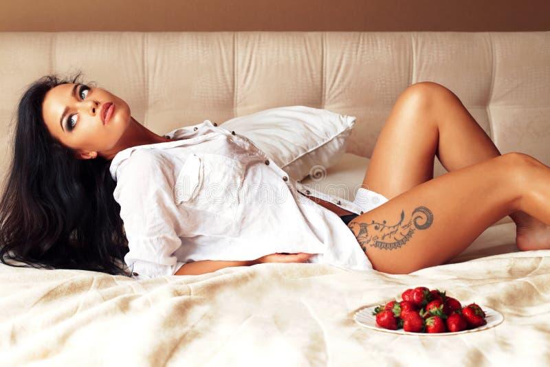 Härlig kvinna med mörkt hår och slank sexig kropp som kopplar av i säng royaltyfri fotografi