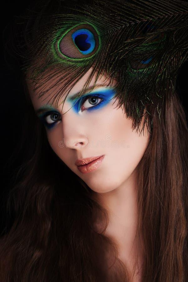 Härlig kvinna med makeup och påfågelfjädern royaltyfria foton
