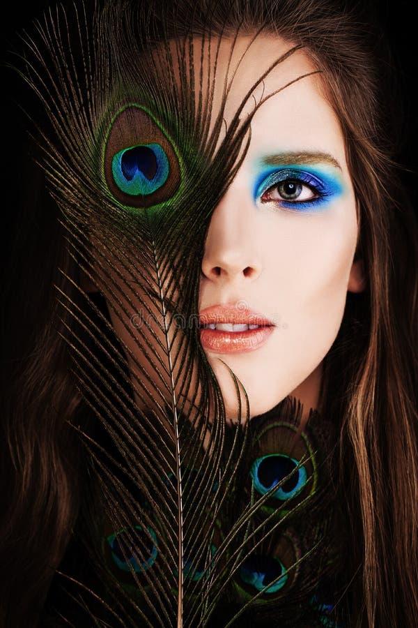 Härlig kvinna med makeup och påfågelfjädern fotografering för bildbyråer
