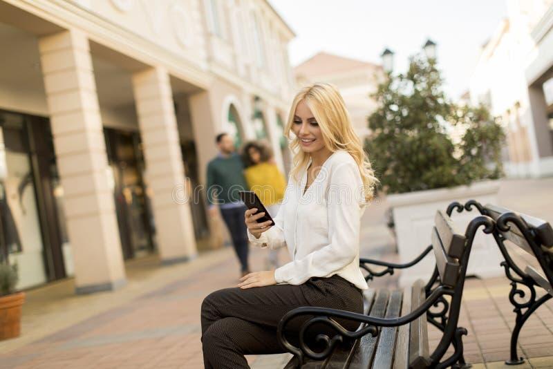 H?rlig kvinna med mobiltelefonen som sitter p? b?nken royaltyfri foto
