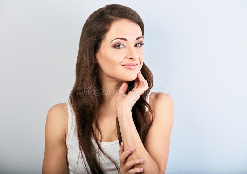 Härlig kvinna med näck makeup och sund skenhud som ser och trycker på framsidan i tillfälliga kläder på ljust - blå bakgrund royaltyfria bilder