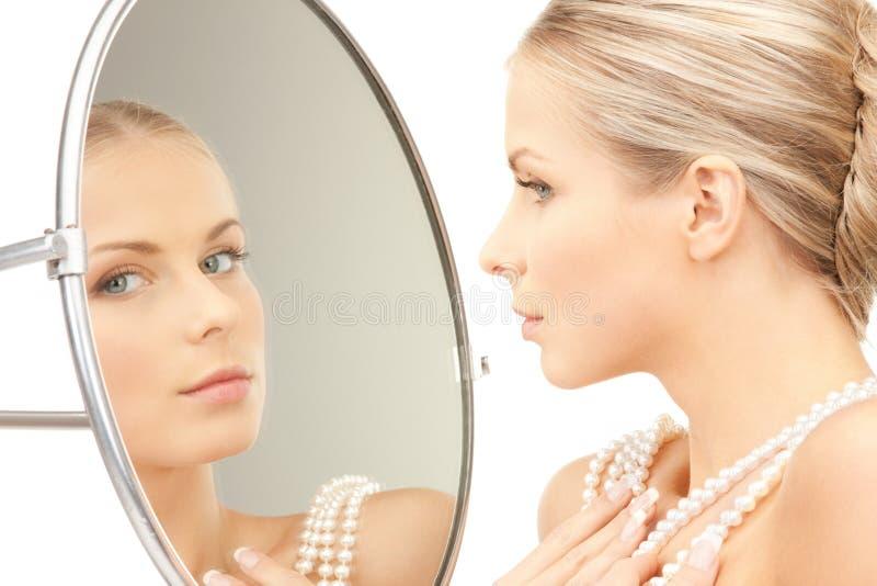 Härlig kvinna med pärlapärlor och spegeln arkivfoto