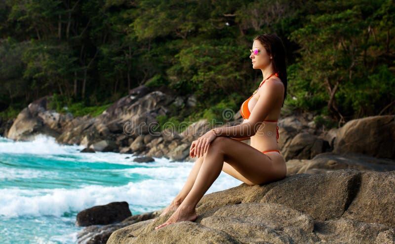 Härlig kvinna med passformkroppen i den sexiga bikinin, tropisk klippa arkivfoto