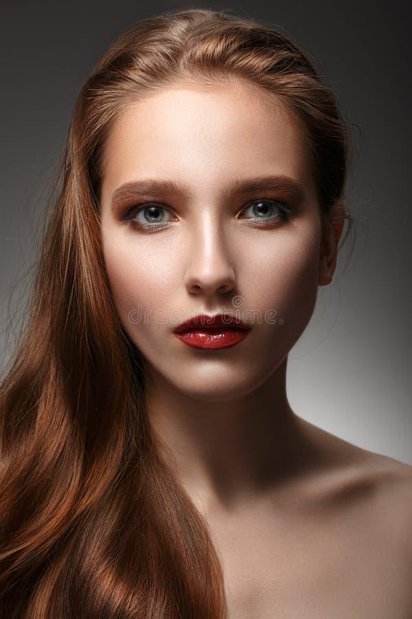 Härlig kvinna med perfekt hud och långt hår på en grå backgr royaltyfri foto