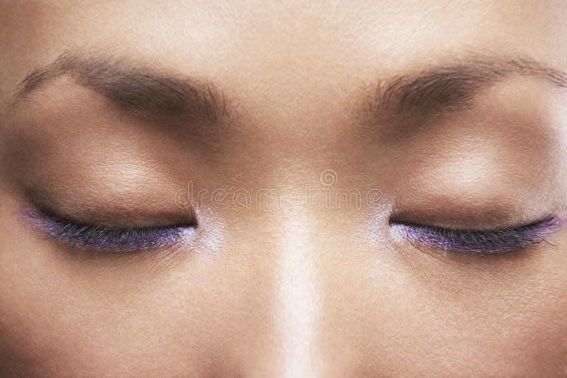 Härlig kvinna med purpurfärgad eyeliner royaltyfria bilder