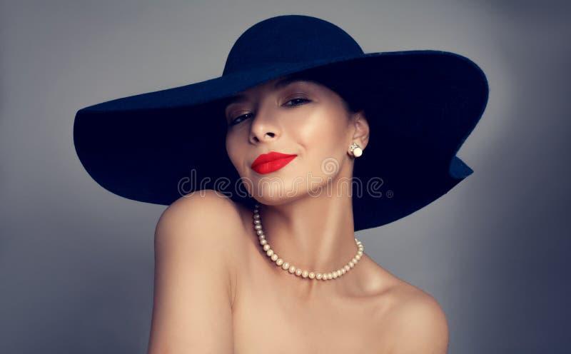 Härlig kvinna med röd kantmakeup och den blåa hatten royaltyfria bilder