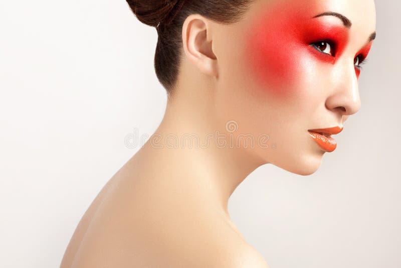 Härlig kvinna med röd makeup och röda kanter. Modemakeup royaltyfria bilder