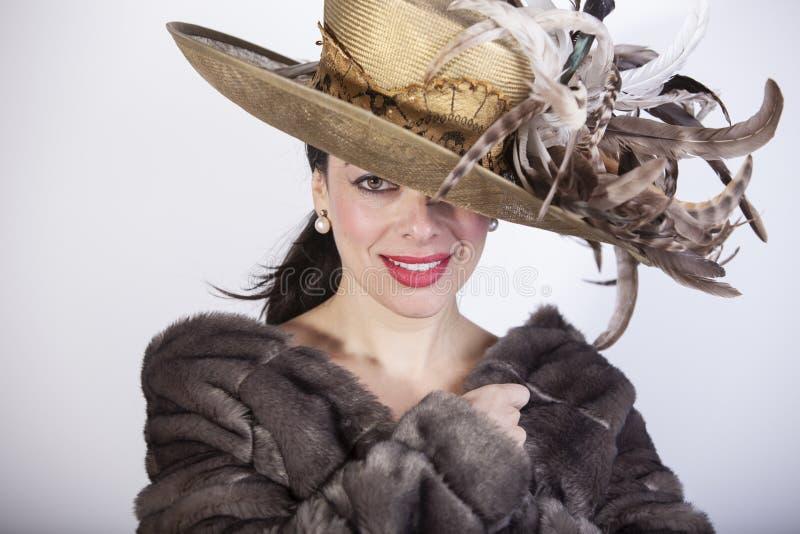 Härlig kvinna med röda kanter som ler med hatten och pälslag och finger i hennes mun som pekar tystnad arkivbilder