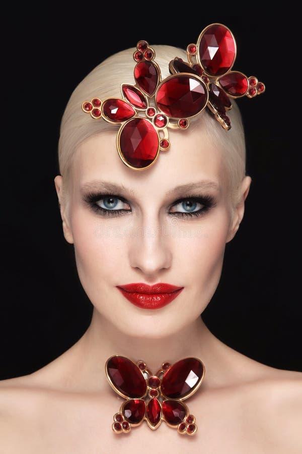 Härlig kvinna med rökig ögonmakeup, röda kanter och utsmyckade fjärilar royaltyfri fotografi