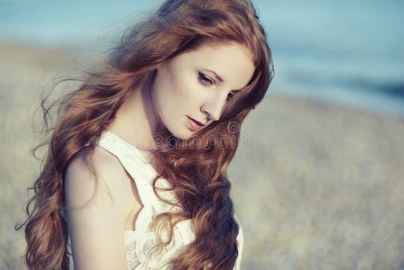 Härlig kvinna med rött hår på havet royaltyfri foto