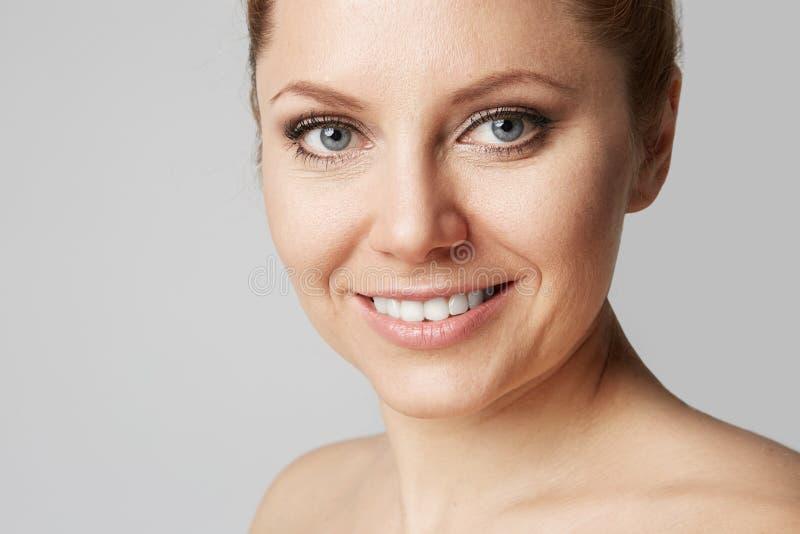 Härlig kvinna med ren hud, naturligt smink och vita tänder på grå studiobakgrund Medicinsk och kosmetisk ansiktsbehandling royaltyfria foton