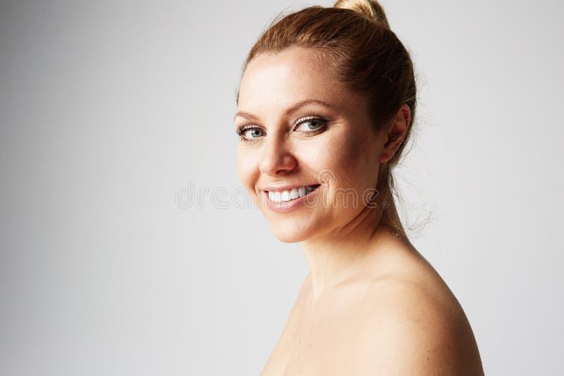 Härlig kvinna med ren hud, naturligt smink och vita tänder på grå studiobakgrund Medicinsk och kosmetisk ansiktsbehandling royaltyfri fotografi