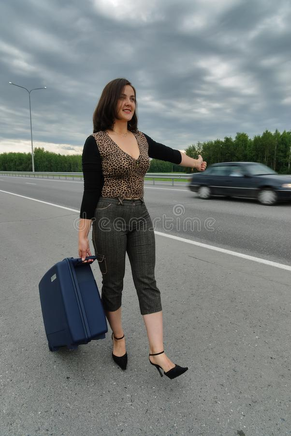 Härlig kvinna med resväskan som stoppar bilar royaltyfri bild