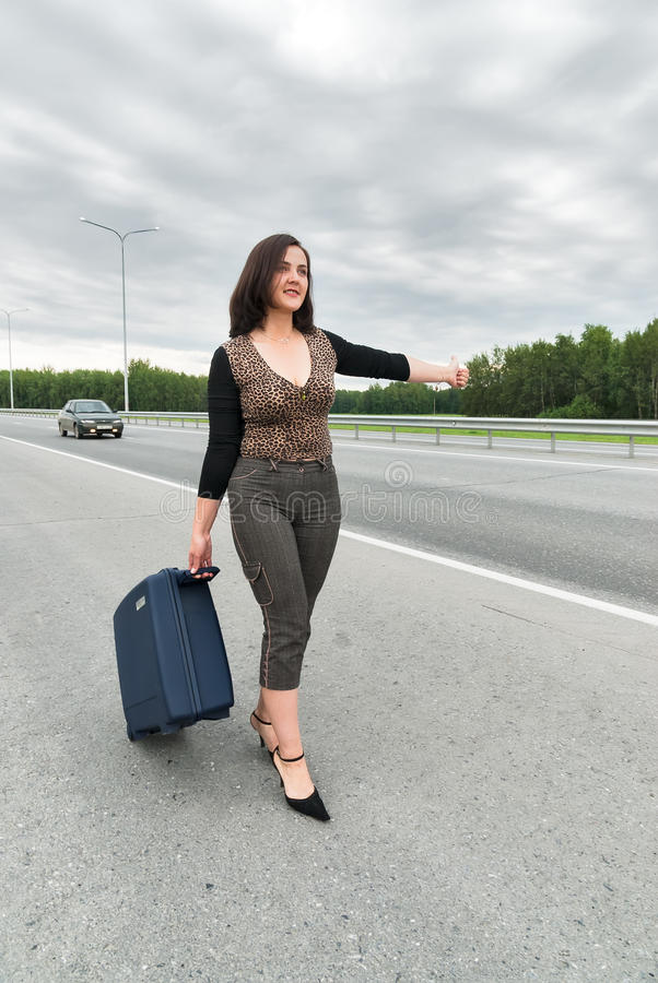 Härlig kvinna med resväskan som stoppar bilar arkivfoton