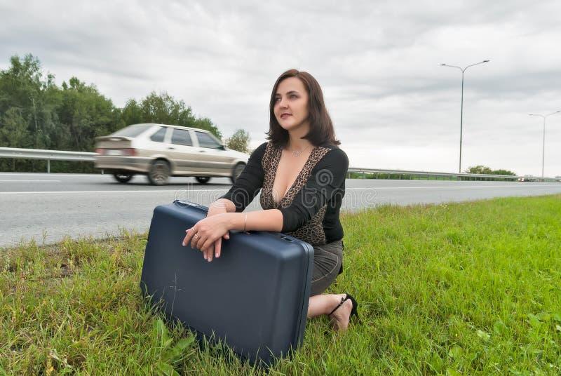 Härlig kvinna med resväskaväntningar på vägen royaltyfria bilder