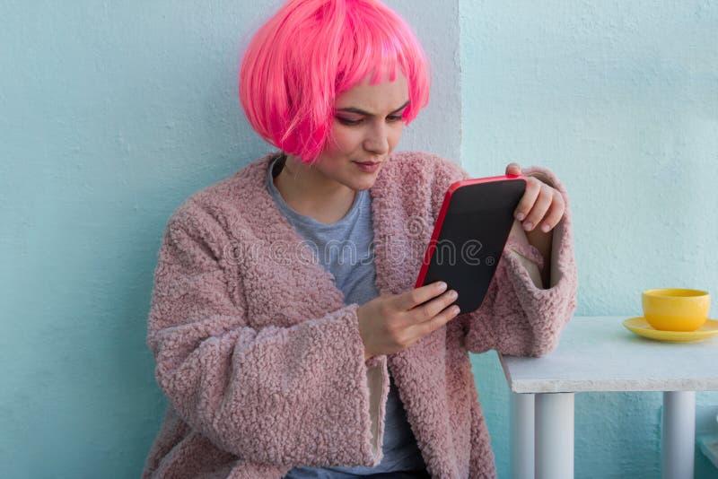 härlig kvinna med rosa hår genom att använda minnestavlan i coffee shop arkivbilder