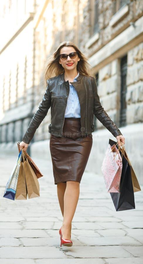 Härlig kvinna med shoppingpåsar i det ctiy arkivfoton