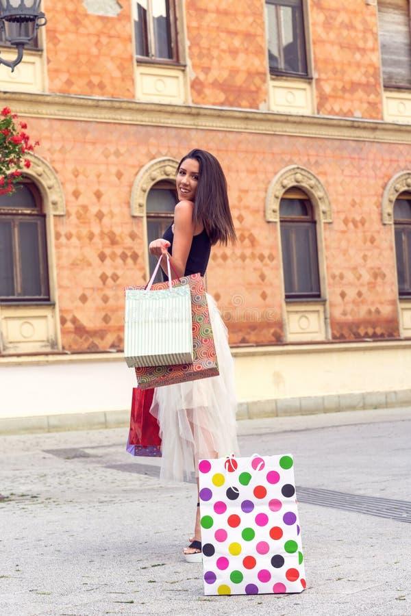 Härlig kvinna med shoppingpåsar på stadsgatan royaltyfri fotografi